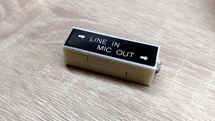 "A small white 3d-printed box with a black label that says ""line in"" and ""mic out""."